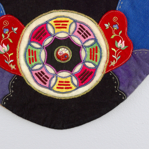 Apron of red cotton, bordered with black band of cotton. One deep front pocket ornamented with applique in felt. Multi-colored silk embroidery showing YIN and YAN and the diagram found in the I-Ching, the book of Changes.