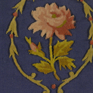 Dark blue satin embroidered in colored wool in a design of a rose spray within a wreath.