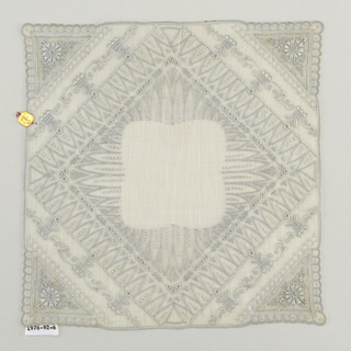Handkerchief with a pattern of a diamond in a square and flowering plants.