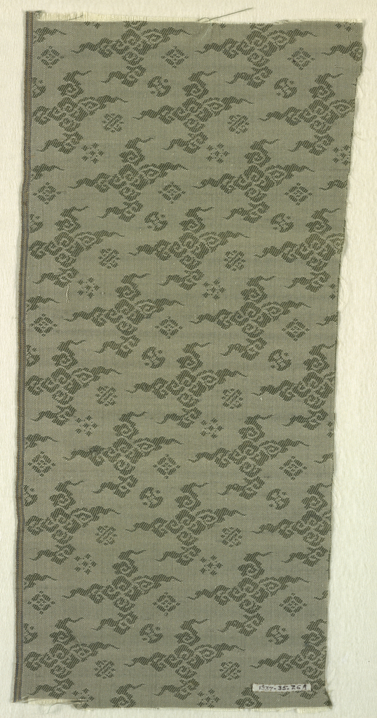 Fragment with white silk warp and green silk weft in an allover small-scale pattern of Buddhist motifs: coin, knot, cloud, jewel, etc. On one side of fabric design worked in warp; on reverse, design worked in weft.