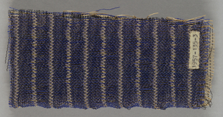 Stiff and shiny synthetic yarns, buff and blue, woven in an interlocking fashion creates two surfaces with an airy, but firm middle section.