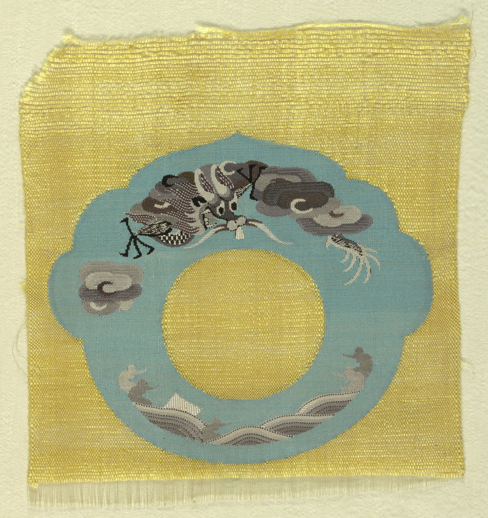 Uncut pieces for costume accessories have a yellow ground with a lobed blue ring containing a dragon, clouds and waves in many shades of gray.