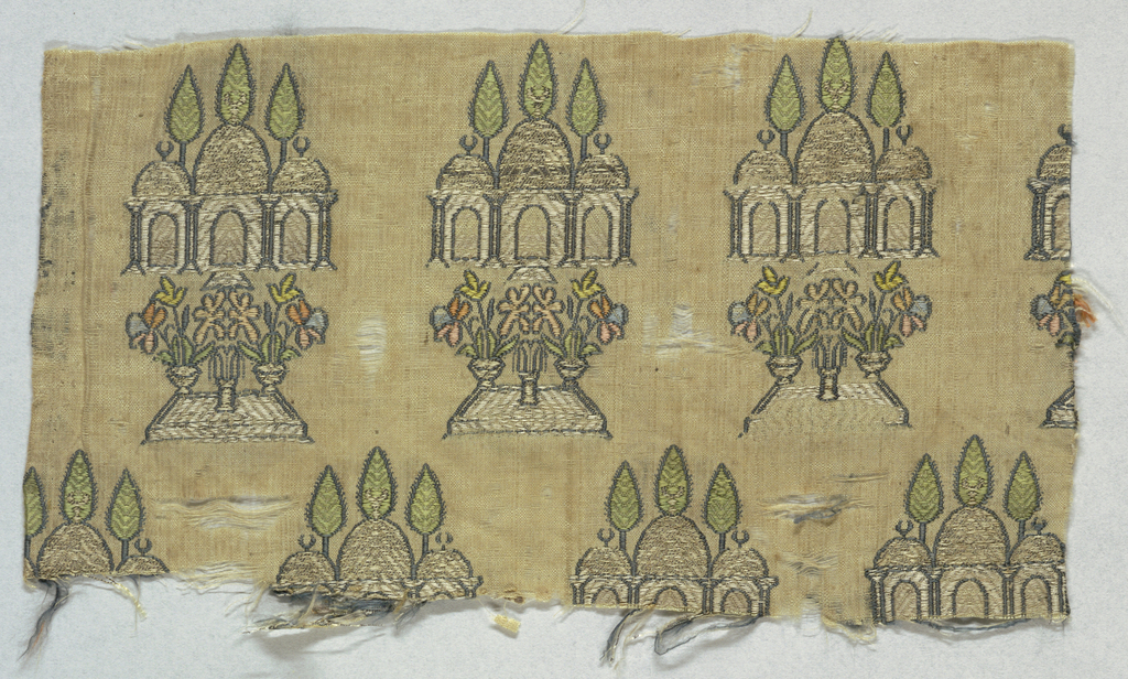 Cream-colored groud with a horizontal repeat of a three-domed mosque above a courtyard with a pool and potted flowers. Brocaded in green, blue, yellow, orange, and pink with silver and gold metallic thread.