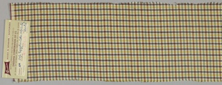 Sample of fine even sided twill with woven shepherd's check of yellow, green, two shades of brown on cream ground. Wide plied cotton cloth selvedges with red and black pencil stripe edges.