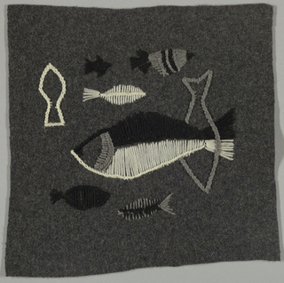Square of dark gray wool embroidered in white, black and gray in an abstract design of fishes.