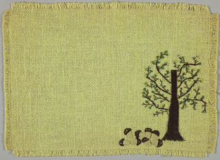 Place mat of light green burlap embroidered in shades of green, brown and mustard in a stylized design of a tree and mushroom.