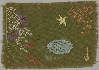 Place mat of dark green burlap embroidered in white, purple, blue, orange-red, green and metallic thread in an abstract fish and seaweed pattern.