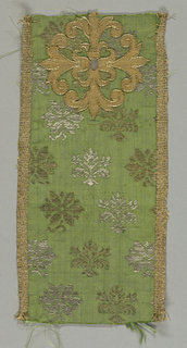 Fragment of a stole or maniple. Gold quatrefoil on fabric of green ground with white (originally silver) and gold floral shapes. Edged with woven metallic tape.