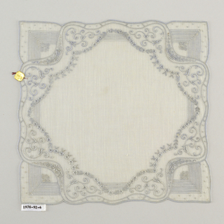 Handkerchief with a pattern of curving scrolls, floral sprays and bars of openwork.