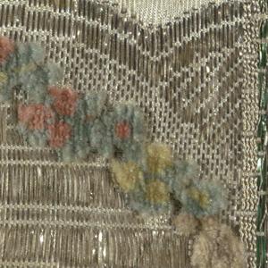Small fragment in cut velvet of a reclining figure under an arch of small flowers. Ground has silver metallic thread.