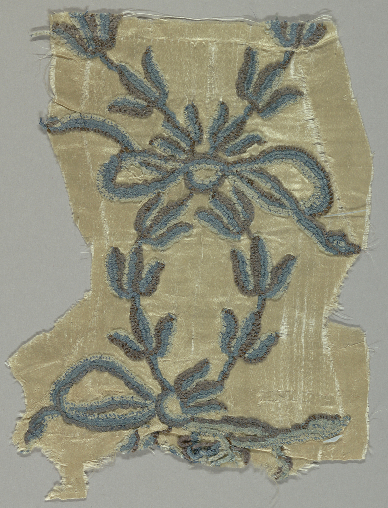 White satin with embroidery in three shades of blue chenille; design, leaves and bowknots.