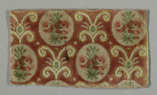 """Small-patterned or """"miniature"""" velvet fragment with a rose cut pile ground and white cut pile medallions, each enclosing a spray of roses in pink, rose, and green, arranged in vertical stripes. Palmettes in white cut pile between medallions outlined by voided ground which is covered by a secondary yellow weft."""