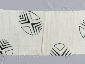 Silk textile sample printed with pattern of black circles composed of triangles and darts, on a white ground.