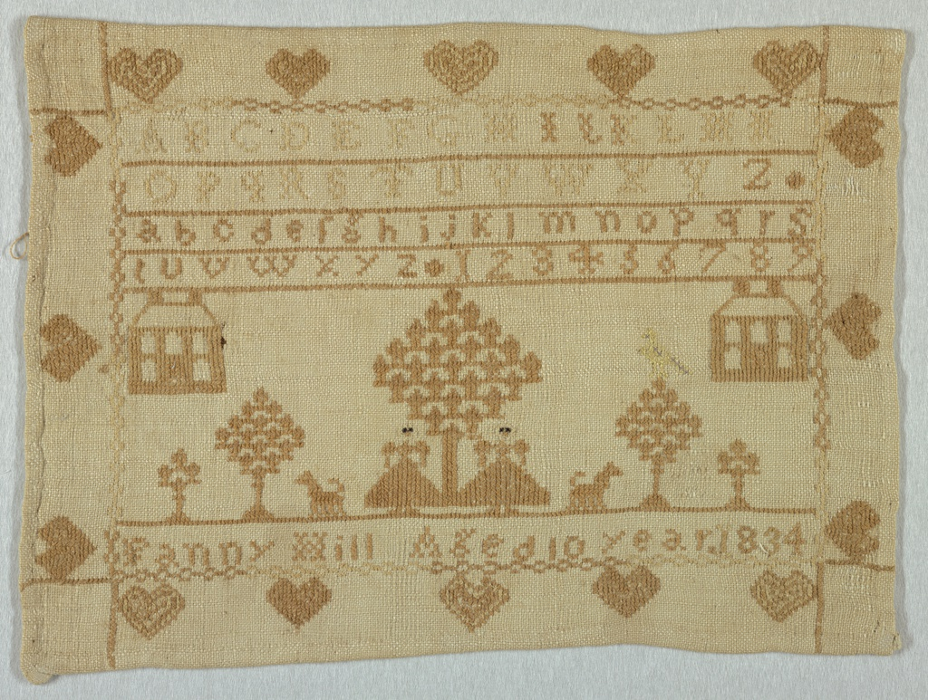 The field contains bands of alphabets and numerals, motifs symmetrically arranged of houses, trees, female figures, and dogs, with the inscription. With a border of hearts, embroidered in brown on a white ground.