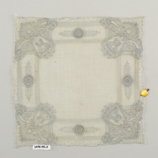 Handkerchief with a pattern of stripes and bars and circular openwork rosettes in the middle of each side. Each corner has a pattern of an angel head under a floral spray over a pair of flowering cornucopias.