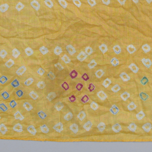 Square bandana with a dyed yellow ground and pattern in resisted white ground, with red, blue and green added by block or brush. Square in center with cross and four half-circles; border of tangent diamonds.