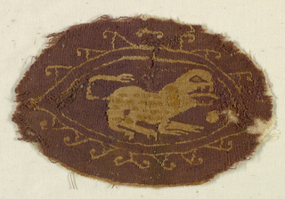 Oval medallion, monochrome, light pattern on dark ground.  Spotted quadruped animals within a leaf-shaped border.