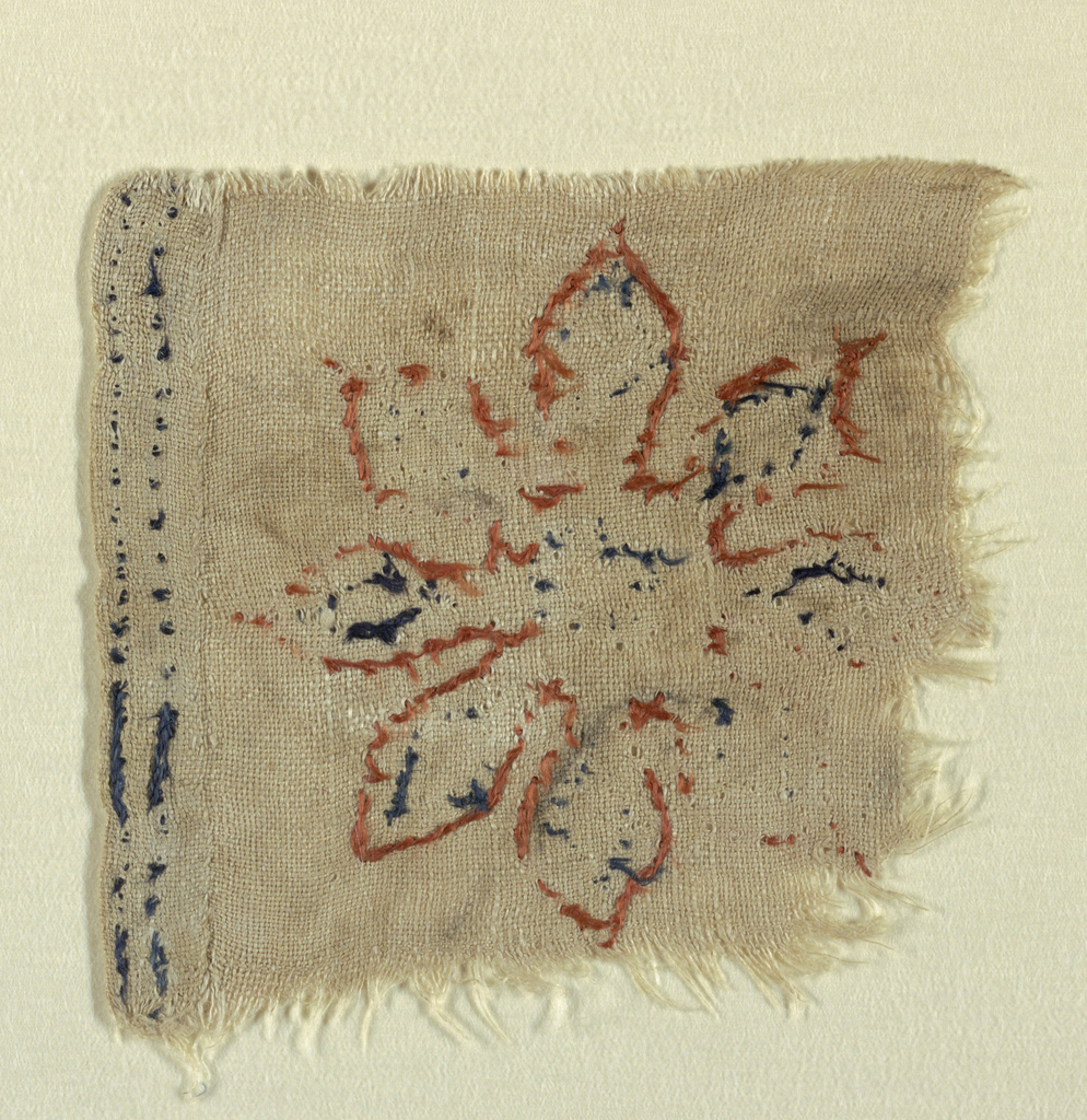 Fragment of linen with large eight-pointed floral rosette in silk chain stitch, with orange outline and with dark blue petals and center outlined within this. Set close to border of double row of dark blue chain-stitch. Plain selvage turned under this and hand-hemmed.