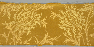 A gold color warp and slightly different gold color weft form a tone on tone floral pattern.
