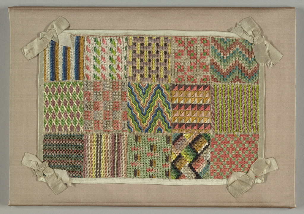 Small embroidered sampler with a grid composition of three by five squares, each with a different geometric  pattern including diamonds, stripes and zigzags; worked in shades of black, brown, grey, light blue, light green, yellow, salmon-pink, and ivory. Bound on all four edges with ivory silk ribbon, with a bow at each corner.