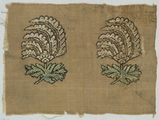 Tan fragment with two cone-shaped floral forms perched over leafy stems. Brocaded in white, green and black.