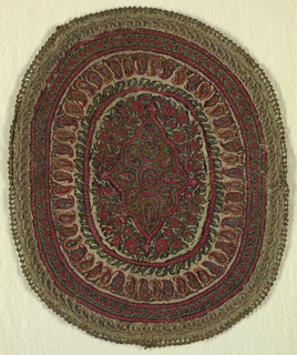 Oval shaped textile with embroidered face finished with green braid and metal edging, lined in printed cotton fabric. Embroidered with central diamond shape borded with band of botehs and vines.