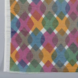 Diamonds with rounded corners overlapping each other in rows. Printed in blue, green, tan, pink, and orange on white. Selvedge on one side and cut on other sides.