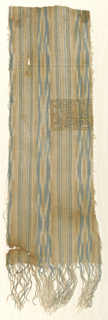 Fragment of a fabric patterned by a group of fine light blue, ivory and light brown stripes alternating with a group of slightly wider ikat stripes either light blue and ivory. Part of a rectangular panel with a gilded Kufic inscription outlined in black. Warp fringe, about 3 1/2 inches long at the bottom.