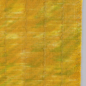 Panel in shades of orange and yellow with random splashes of green moving diagonally across the face of the textile. Warp fringe on both ends with vertical ribs at regular intervals.