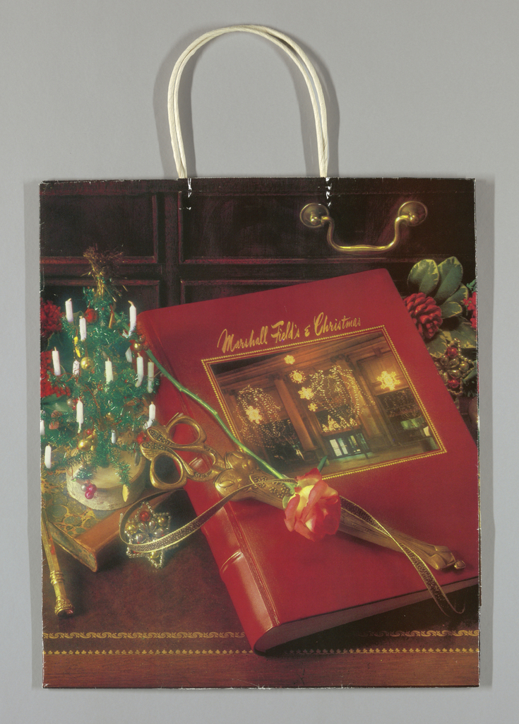 "Photo of store entrance, a rose, Christmas decorations and a red leather album.""Marshall Field's"" and "" Christmas"" in script on album. Design continues in side panels."