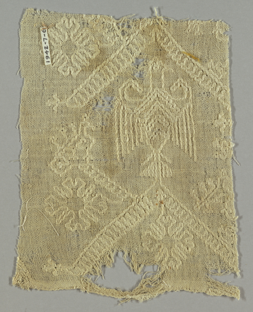 Fragment of white-on-white embroidery showing an eagle, diagonal bands and flowers.