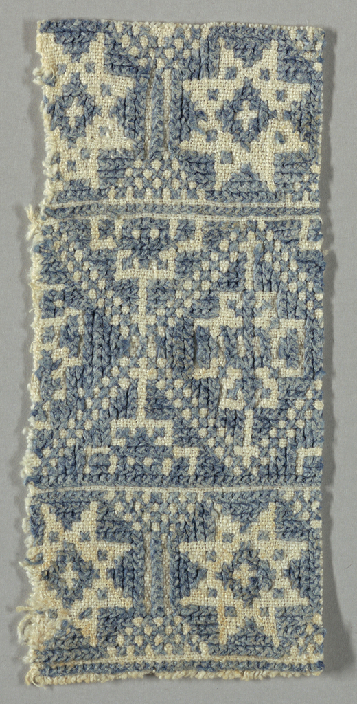 Design of lozenges and eight-pointed stars worked in blue cross-stitch on a white ground.