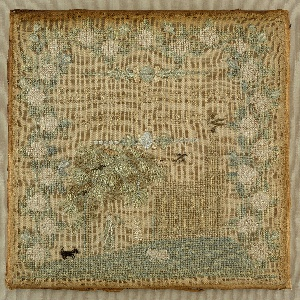 Small square sampler embroidered in pale silks on a natural linen ground. The central image is of a church with a steeple on a hill, with a tree, two girls, a dog and a sheep. A deep border of white roses surrounds the scene on three sides.