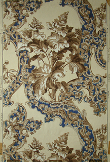 Rococo revival style. Scrolling ribbons and foliage create a diaper framework. Large-scale flowering plant grows within the framework. Printed in blue, white and tan on off-white ground.