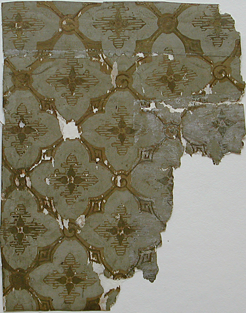 """Small wallpaper fragments, diamond pattern containing stylized cross-shaped four-petal flowers backed by larger cross-shaped area forming four fleur-de-lis. Printed in putty, tan and gold. Parts """"a"""" and """"b"""" are joined together."""