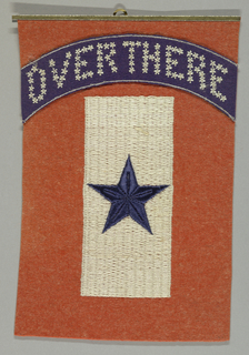 """Rectangular red wool felt banner appliquéd with a navy blue arch across the top, on which """"Over There"""" is embroidered in small white stars. Underneath the arch is an embroidered white rectangle with a navy blue five-pointed star in the center. A metal rod with a hook holds the piece at the top. During World War I, banners like this were hung in the window of a home to denote that a family member was serving in the U.S. military."""