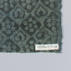 Fragment printed on both sides in black over a greenish-blue ground. Design on one side shows open flower faces with pointed leaves, stems and foliage curving around flower heads to form active open frame. On reverse side a small block design framing small flower head alternating with one selvage present.