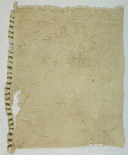 White cotton embroidered in white in angular pattern showing birds and other forms. Ball fringe on part of one side.