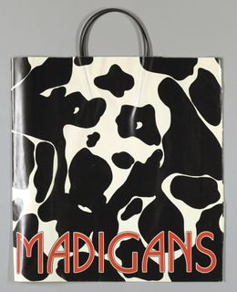 "Spotted black and white cow print on white background; ""Madigan's"" in large red letters across bottom. Design continues in side panels."