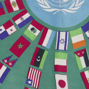 United Nations emblem in center surrounded by radiating spokes of flags of many countries on a green background.