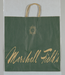 Clock design, with time set at 3:00 and store name in script. Natural brown on dark green paper.