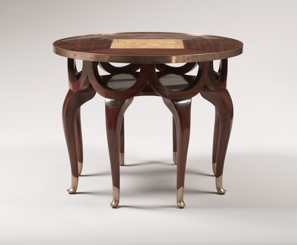 Eight-legged table with a frieze of conjoined demi-lune swags of wood under the round table top resting on the legs. The table top is centered by a square of iridescent yellow glass tiles surrounded by striated grained veneered wood panels.