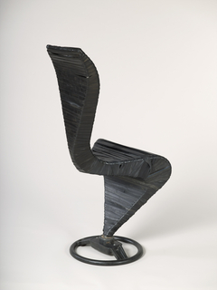 High backed S-shaped steel frame chair on black steering wheel base; multiple narrow horizontal strips of recycled black rubber inner tube stretched over frame.