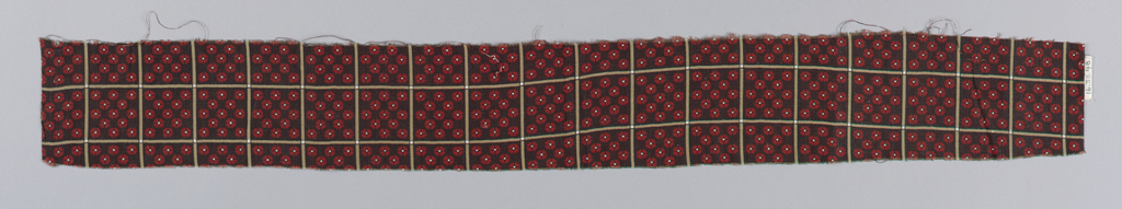 Black ground with a regular grid formed by intersecting light brown lines. Each square is filled with tiny red and white four petal flowers.