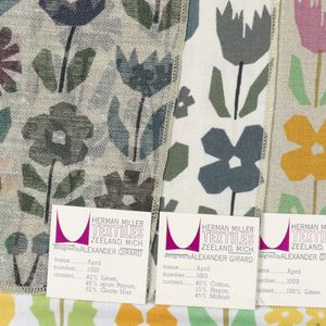 Multicolored stylized flowers printed on white. Eleven smaller samples in other colorways are attached across the top of the large sample. All samples are serged on four sides.