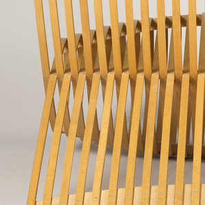 Wide reclining chair formed of looped strips of bent beachwood. Strips loop back on themselves to form a broad ovoid seat.