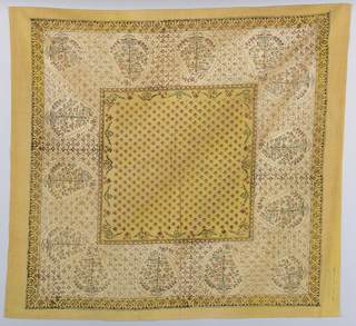 Handkerchief with a central yellow square and yellow border has a design of large paisleys in the off-white field. Paisleys are surrounded by small geometric pattern of squares, crosses, dots and dashes. Central yellow square has small red squares outlined in black and a border of a trailing flower and vine pattern.