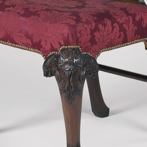 The pierced back splat and crest carved in rococo style with foliate decoration; the knees of the front cabriole legs with carved rococo foliate scroll decoration descending to hairy paw feet. The tapered and raked rear legs with stretcher between. Upholstery replaced.