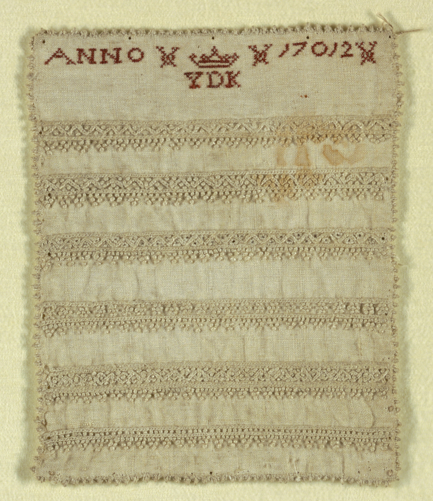"""Six cross borders, geometrical patterns in embroidery; initials """"YDK"""" crowned """"ANNO 17012""""; edged with small knots."""