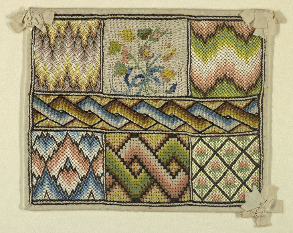 Sampler divided into seven compartments; five showing geometric designs and two floral. Mounted on heavy paper and bound with white silk ribbon, bows at three corners. One ribbon missing.